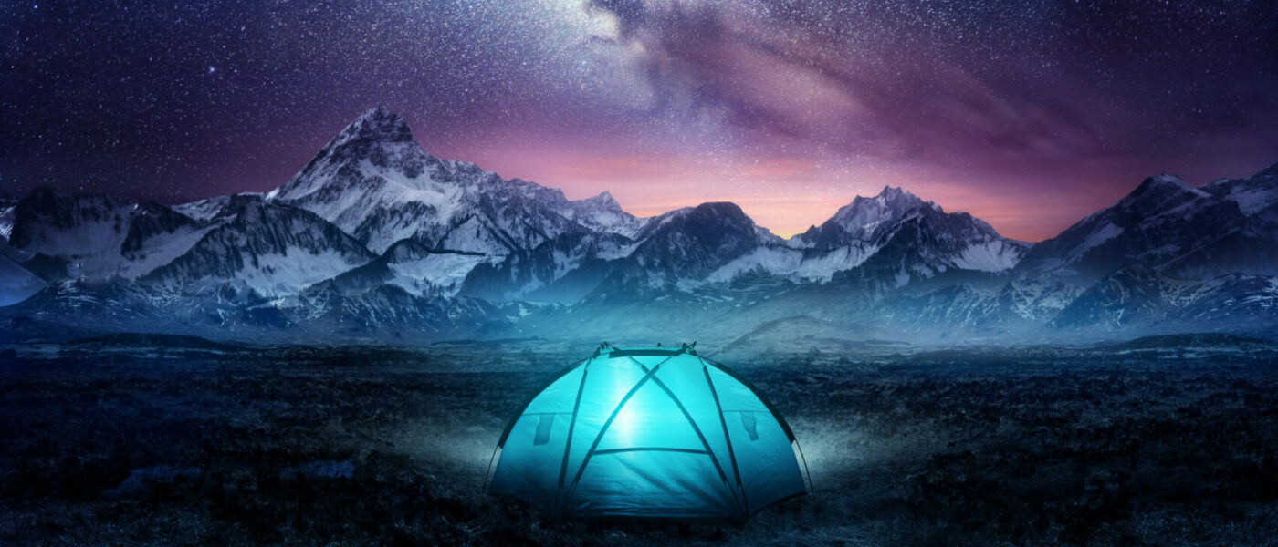 Camping in the mountains under the stars. A tent pitched up and glowing under the milky way. Photo composite.
